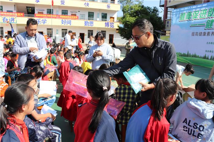 五、市疾控中心副主任罗海光正在给学生们发放文具包1.JPG